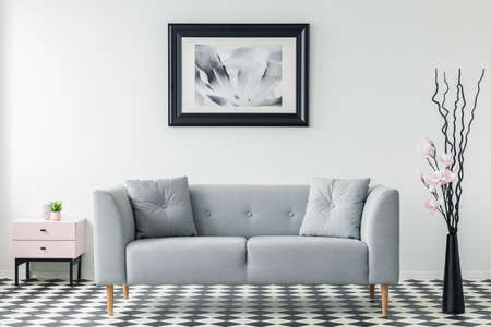 Real photo of a simple sofa with pillows, poster on the wall and branches in the a vase in a living room interior Stok Fotoğraf - 106250612