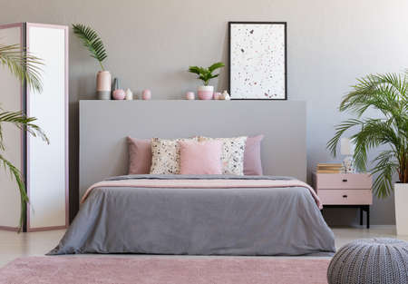 Poster on grey headboard of bed in grey and pink bedroom interior with plants. Real photo