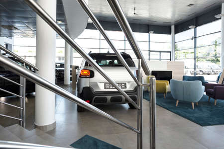 Waiting corner with armchairs, TV and soft carpet in elegant car showroom interior in the photo with handrail in the foreground