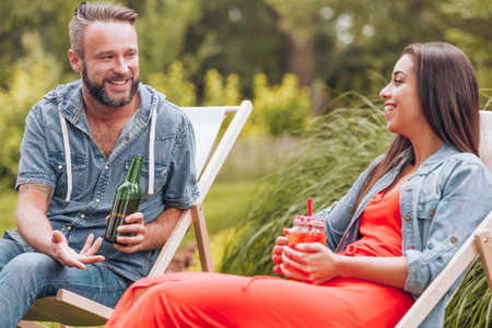 Smiling woman and happy man drinking beer and cocktail while relaxing on sunbeds