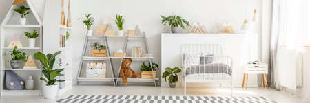 Real photo of child's bedroom interior with shelves, plants, striped carpet, teddy bear and bed Archivio Fotografico