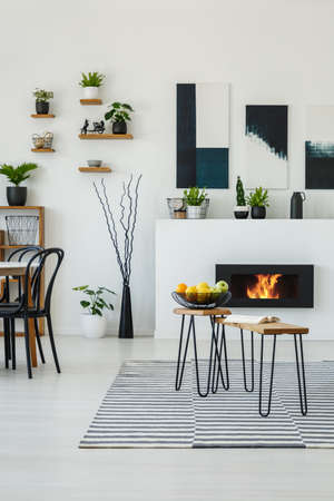 Tables on patterned carpet in white living room interior with posters above fireplace. Real photo