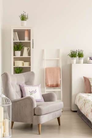 Grey armchair with a pillow, ladder with a blanket and shelf with decorations in a bedroom interior. Real photo