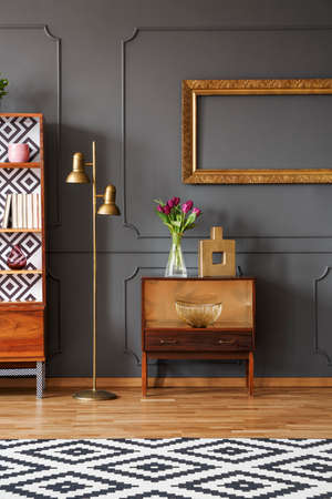 Golden painting frame on a dark wall with elegant molding, a brass floor lamp and a vintage wooden cabinet with tulips bouquet in a stylish living room interior