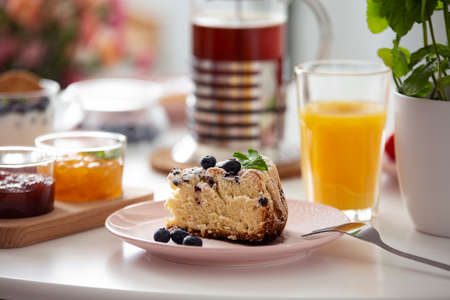 Close-up on cake on plate on a table with orange juice during breakfast. Real photo with blurred background