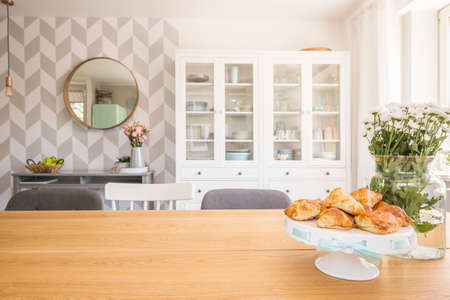 Croissants on wooden dining table in white apartment interior with flowers and mirror. Real photo Stock Photo