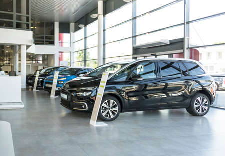 Shiny cars standing in a row in bright elegant car rental interior with windows on wall Stock Photo