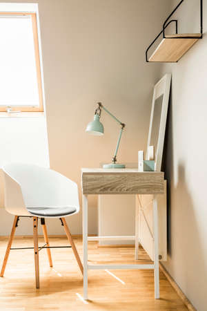 Lamp on desk in white workspace interior on attic with chair and window. Real photo