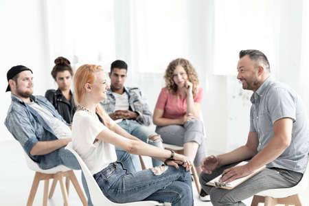 Smiling red-haired girl talking to a therapist during meeting for difficult teenagers