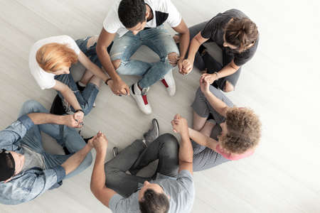 Top view on teenagers sitting in a circle and holding hands during group therapy