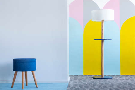 Real photo of a blue stool and a modern lamp in bright living room interior with colorful arches on the white wall. Place for your poster