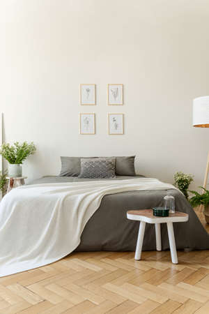 White blanket on grey bed in bright bedroom interior with posters and wooden table. Real photo Stock Photo