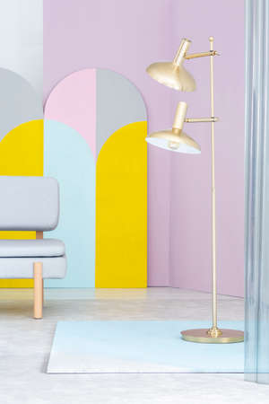 Real photo of a golden floor lamp and a gray sofa in colorful living room interior with geometric plywood arches as decoration Stock Photo