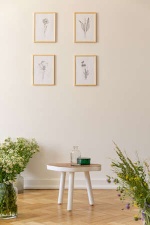 Posters on white wall in living room interior with flowers and wooden table. Real photo Stock Photo
