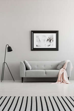 Poster above grey sofa with pink blanket in living room interior with lamp and striped carpet. Real photo