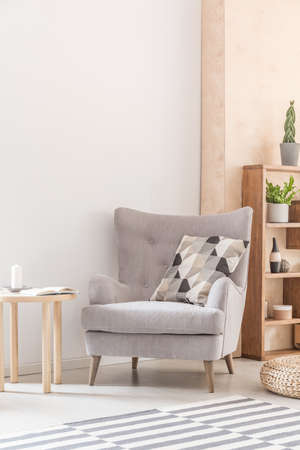 Comfy armchair with patterned pillow next to a wooden coffee table in a living room interior. Real photo. Place your poster here