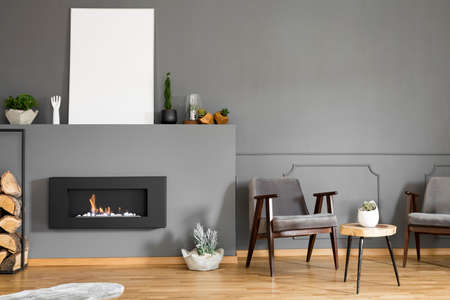 Real photo of two armchairs standing next to a stool and a fireplace with a mockup poster in dark living room interior