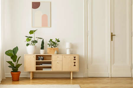 Retro style, wooden sideboard with green plants and a poster on a white wall in a simple apartment interior with herringbone hardwood floor. Real photo. Stock Photo