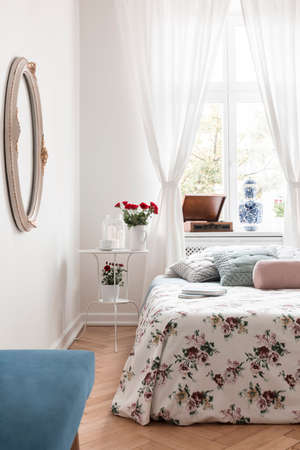 White bedside table with fresh red roses, candles and coffee cup in real photo of bright bedroom interior with window with curtains Stock Photo