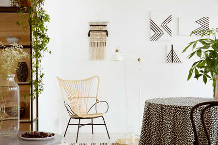 Real photo of a garden chair standing against white wall with macrame and monochromatic paintings in boho living room interior
