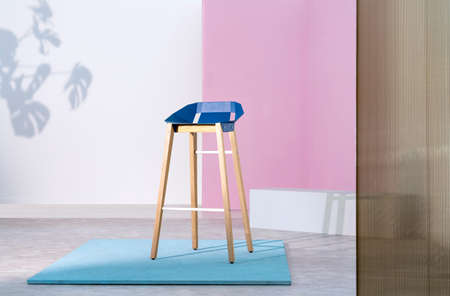 Real photo of a wooden bar stool with a blue seat standing on a piece of plywood in pastel pink studio interior with white accents