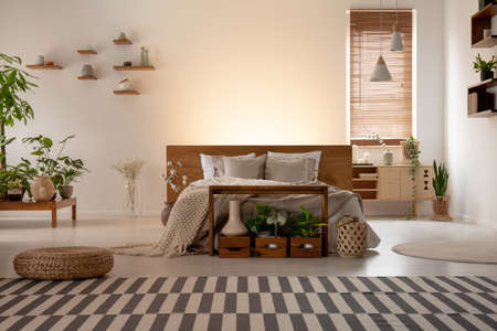 Real photo of an eco bedroom interior with a double bed, striped carpet, plants, lamps and empty wall in the background. Place your painting