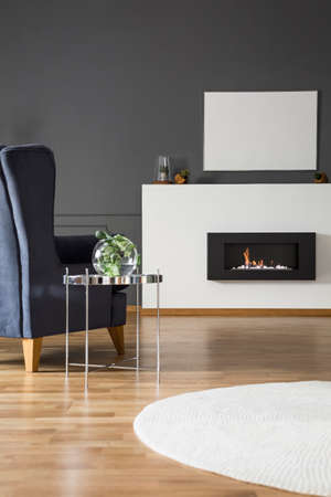 Real photo of a comfy armchair standing in front of a bio fireplace and mockup poster in grey living room interior Stock Photo