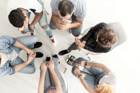 Top view on young people listening to psychologist during meeting of support group Stock Photo