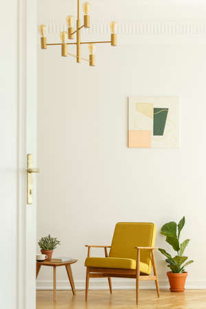 Comfortable yellow chair with a wooden frame in a tall and spacious living room interior with a poster on the white wall. Real photo