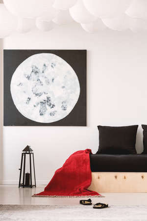 Red blanket on black wooden bed in white bedroom interior with moon poster above lantern. Real photo
