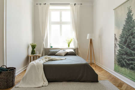 Blanket on dark bed in bright bedroom interior with flowers, lamp and drapes at window. Real photo