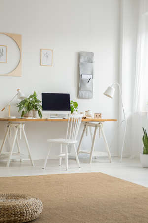 White chair at desk with desktop computer in home office interior with pouf on carpet. Real photo Stock Photo