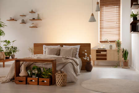 Simple double bed, table, boxes with plants, window blinds next to an empty wall in a bedroom interior. Real photo Stock Photo