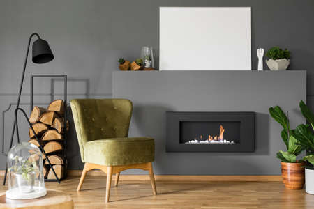 Real photo of a green armchair standing next to a black lamp and bio fireplace with plants and mockup poster in living room interior
