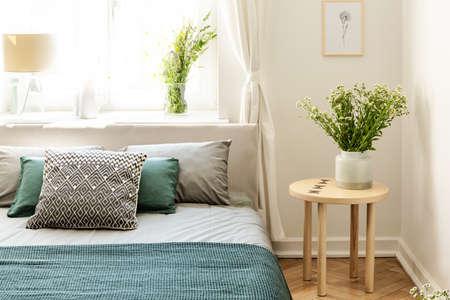 Blumen auf Holztisch neben dem Bett mit Kissen und grünen Laken im Schlafzimmerinnenraum. Echtes Foto