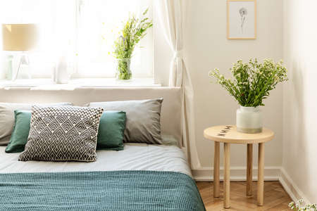 Flowers on wooden table next to bed with pillows and green sheets in bedroom interior. Real photo