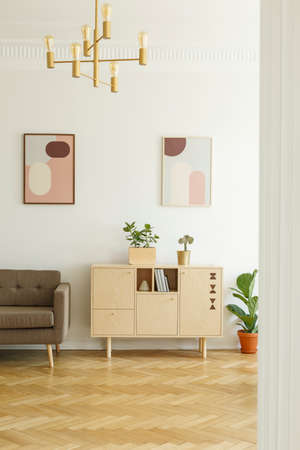 Posters on a white wall, comfy sofa and a simple, wooden cabinet in a real retro living room interior with herringbone parquet floor