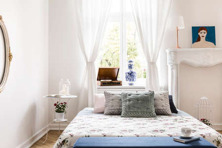Window with drapes in real photo of white bedroom interior with king-size bed with pillows, retro gramophone on windowsill and bedside table with fresh flowers and candles Stock Photo
