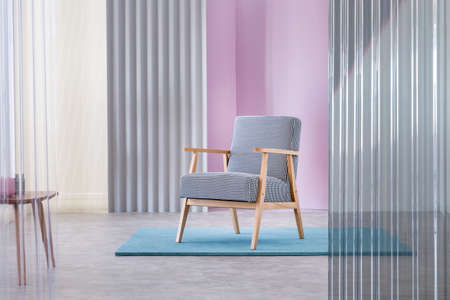 Real photo of a wooden, upholstered armchair with houndstooth pattern standing in the middle of a pastel studio interior