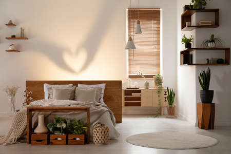 Real photo of a warm bedroom interior with a bed, table, wooden boxes, shadow on the wall and plants