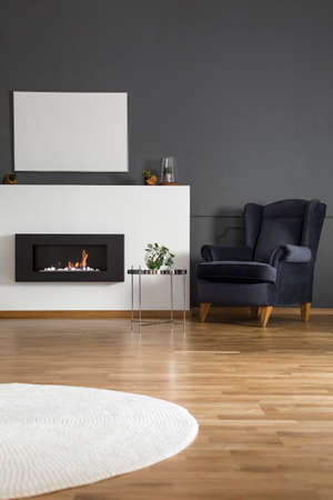 Real photo of a big, comfy armchair standing next to a small table, bio fireplace and mockup poster in dark living room interior Stock Photo