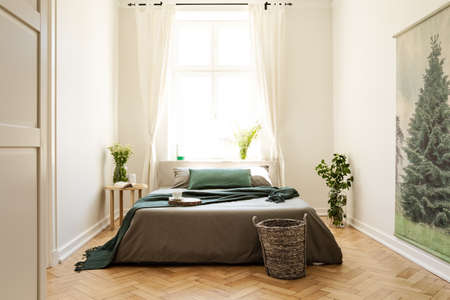 Green blanket on bed and plants in bedroom interior with window and tree painting. Real photo
