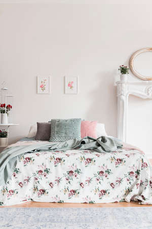 Two simple pink posters hanging on the wall above double bed with cushions and floral sheets in real photo of white bedroom interior