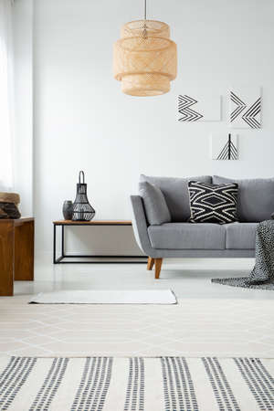 Real photo of a rattan lamp hanging above a gray settee with a black and white cushion in scandi living room interior