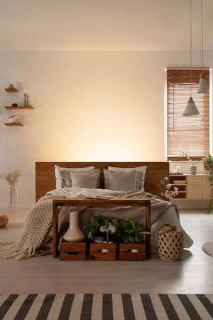 Front view of a double bed with pillows and headboard, table and wooden boxes in a natural bedroom interior. Real photo. Place your graphic Stock Photo