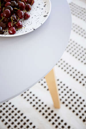 Close-up of a white plate with cherries on a wooden dining table. Real photo