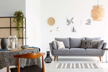 Real photo of a bright and cozy living room interior with patterned pillows on gray sofa and a wooden chair at a dining table