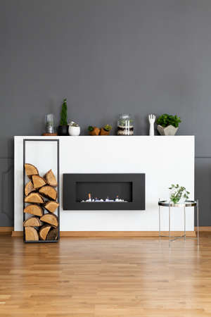 Real photo of a bio fireplace and some wood in dark, simple living room interior