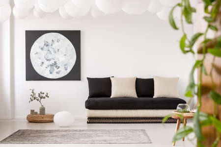 Pillows on black sofa in white living room interior with moon poster and grey carpet. Real photo Stock Photo