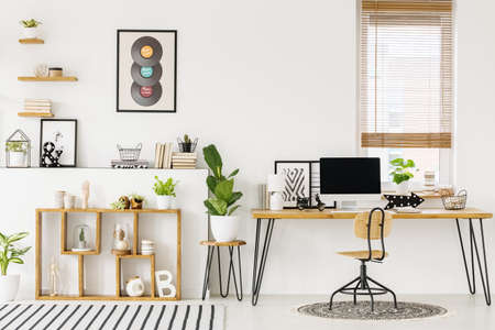Hipster, white home office interior with natural, wooden furniture, industrial elements, green plants and a computer on a big desk